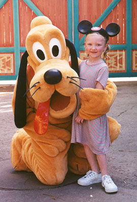 Autumn poses for a photo with Pluto.  She is soaked from going on the water ride 3 times