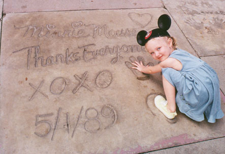 Autumn puts her hands and feet in Minnie's handprints and footprints